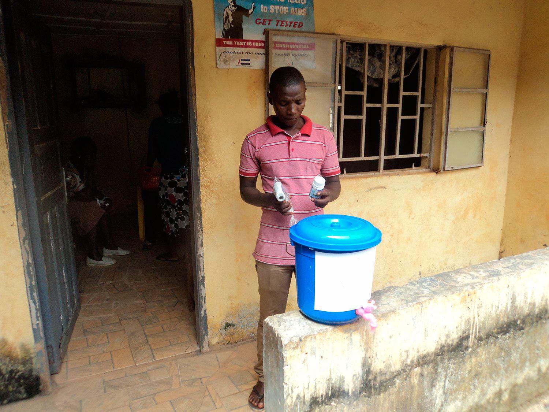 Equipement d'un centre de santé de Freetown avec un seau de désinfectant